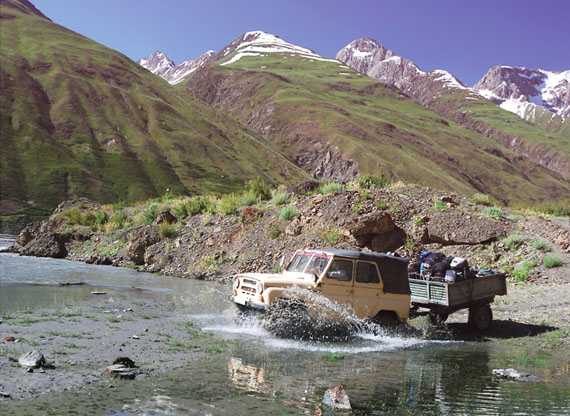 Off-road vehicle and trailer crossing a river with Timbren Axle-Less Trailer Suspension.